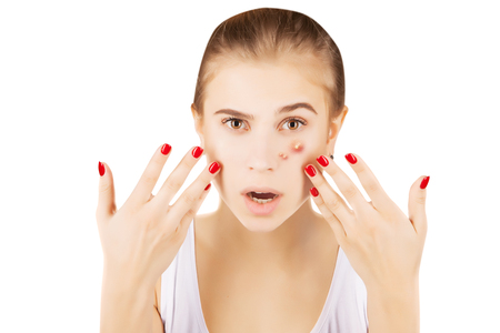 girl with funny disgusted face examines her pimples Stock Photo