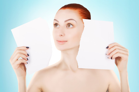 over the edge: young red haired woman with white paper, space for text