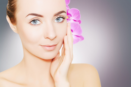 portrait of young european woman with clear skin and purple orchid flower in coiffure  Stock Photo