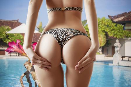 closeup female buttocks tanning near pool