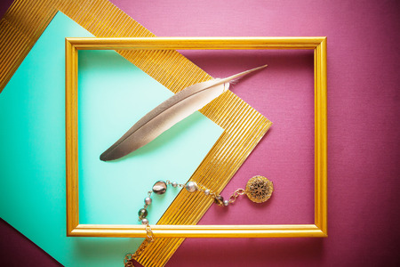pile of old papers with vintage feather pen and golden frame on colorful background