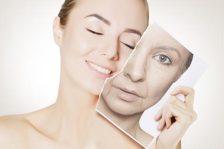 primer plano, retrato, de, mujer joven, cara, tenencia, retrato, con, viejo, arrugado, cara Foto de archivo