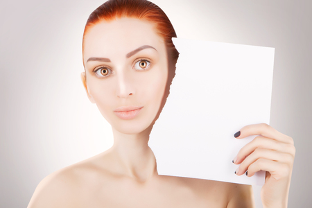 young red haired woman with white paper, space for text