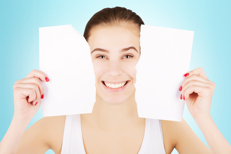 smiling excited blond woman breaks blank paper and holds close to her face