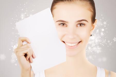 smiling blond girl peeking white paper