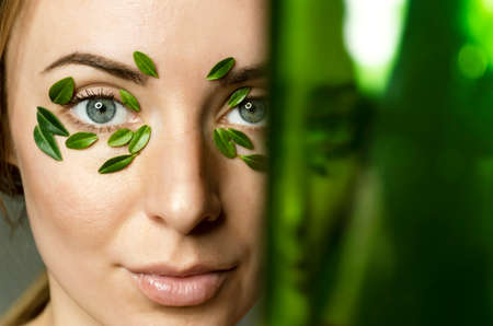 Closeup of young woman`s eyes with boxwood leaves patch with blurred green copy space. Spa and wellness concept template banner for design.