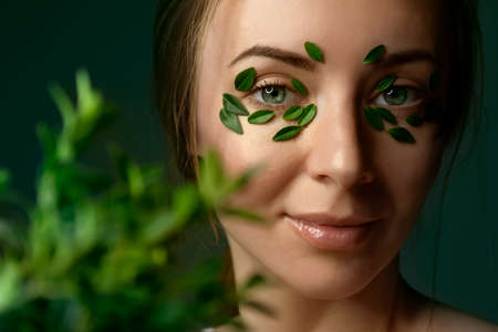 Closeup of young woman's face with boxwood leaf patches. 版權商用圖片