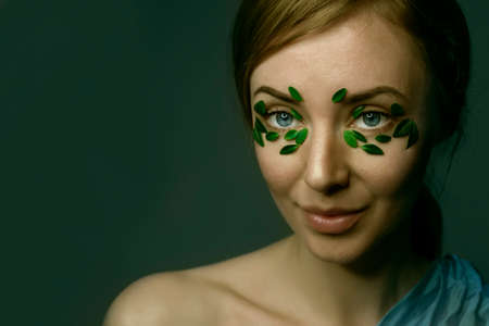 Closeup of young woman`s face with boxwood leaf patches. Spa and wellness concept template banner for design. Cosmetic product advertising