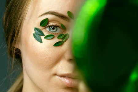 Close up of young woman's face with boxwood leaf patches.