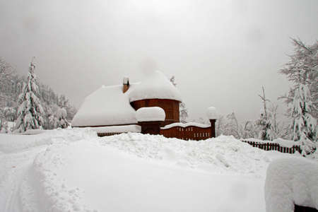 A lonely, snow-covered wooden house on the hillside photo