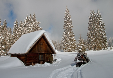 A small, wooden, snow-covered cottage in winter photo