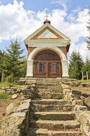 A little chapel standing in the forest Stock Photo - 13865437