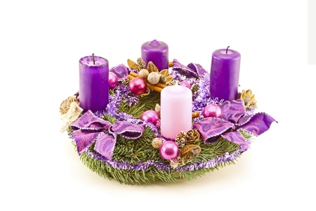Advent wreath decorated with purple candles and christmas ornaments