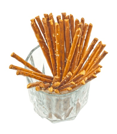 A handful of salty sticks in a glass isolated on white background