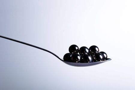 spoonful: A spoonful of metal balls on a light gradient background. Stock Photo