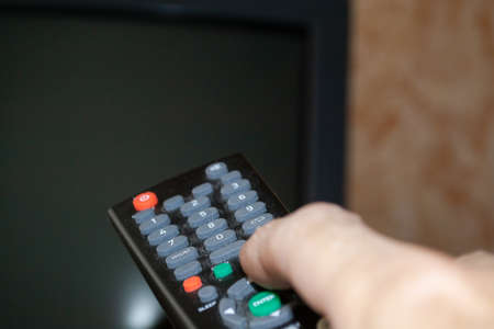 TV remote control with buttons in a person's hand