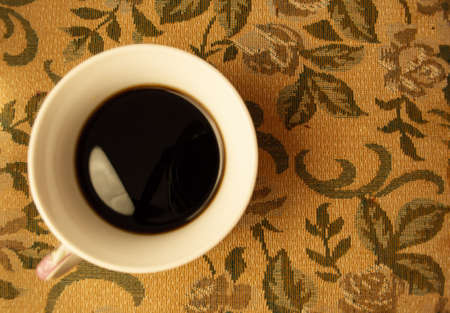 white Cup with black coffee on the yellow table.