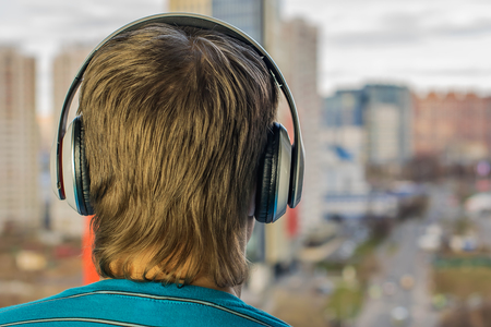 guy in headphones are an audiophile, listening to music in big headphones on the background of city