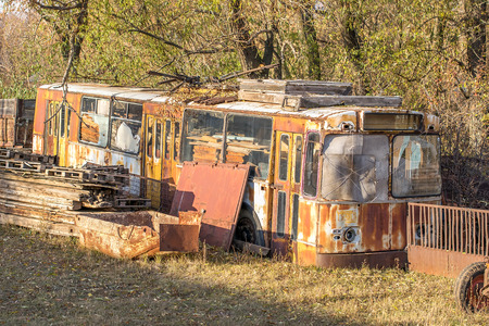 old broken rusty trolleybus in the form of scrap metal in a dump