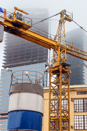 a crane at a construction site in foggy weather, on the background of the unfinished skyscrapers 版權商用圖片