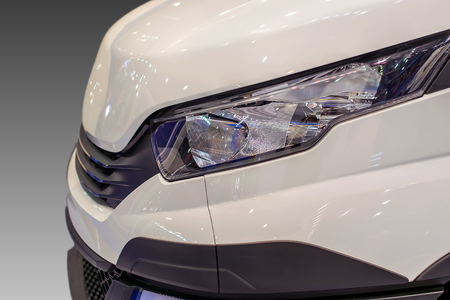 Front of the luxury car: a headlight and a bumper, a radiator and a hood. Stok Fotoğraf
