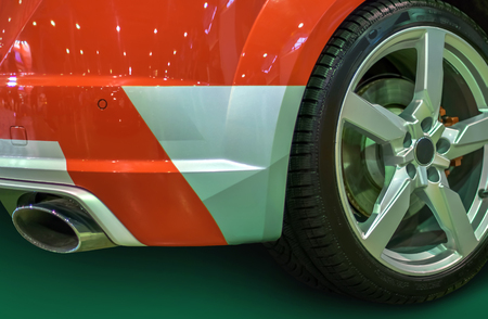 wheel with titanium disc and a racing tire and the rear bumper section and trunk of a red sports car, shining with a sparkle in the spotlight auto show stand exhaust pipe with silencer