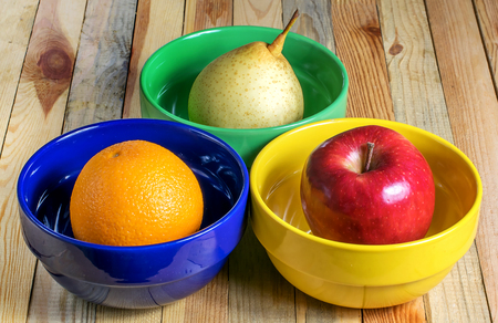 fresh fruit in multicolored plates, delicious tasty and healthy food vegetarian food Apple, pear and orange Banco de Imagens