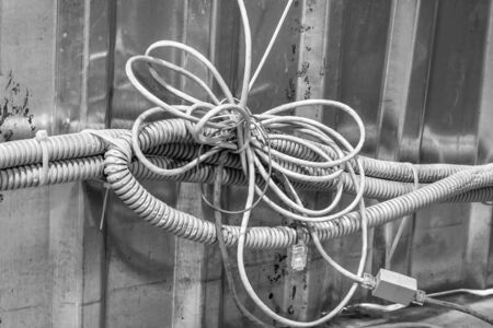 bundle of tangled wires with switches, communication cables and corrugated hoses on the background of a tin profile sheet bnw Stock Photo