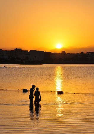 Young man and woman at sunset dive  Egypt  photo