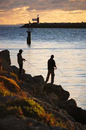 Two fishermen fish off the rocks at sunset in Fremantle, Australia photo