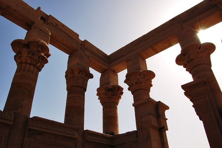 Column ruins at Philae Temple in Egypt backlit by the sun. photo