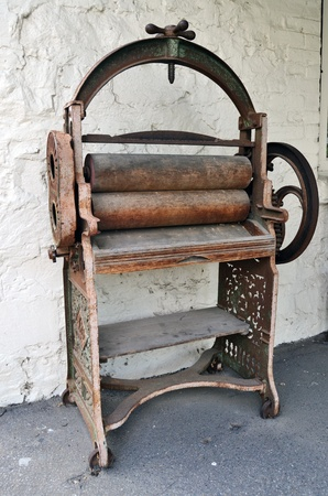 A rusty old hand operated printing press machine photo