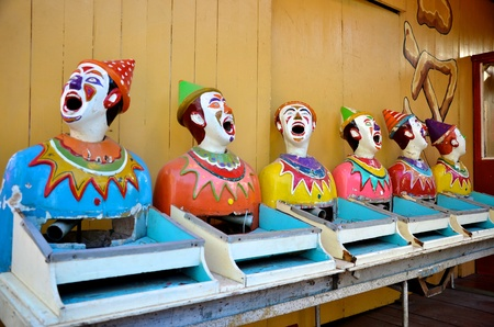 head toy: Row of old laughing clowns at an amusement park