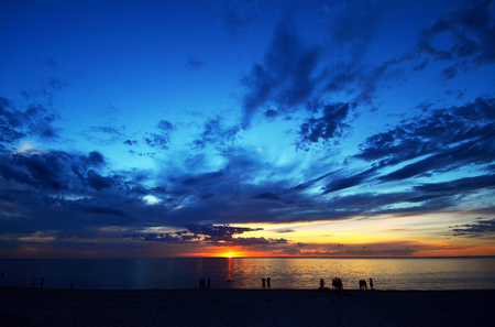 A dynamic sky sunset with silhouettes at the beach photo