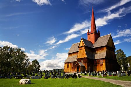 Wooden church and a cemetery in Norway on a sunny day photo