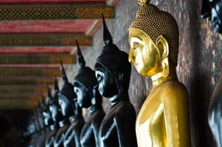 Golden Buddha between black Buddhas, Wat Pho, Thailand  photo