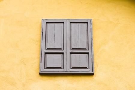 wood window on yellow wall photo