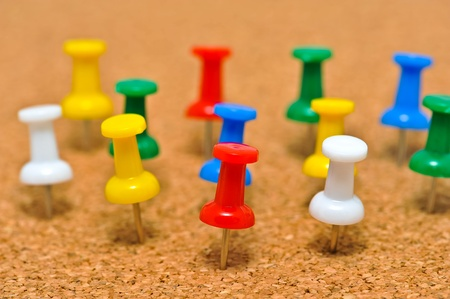 noteboard: Group of colorful push pins on cork bulletin board