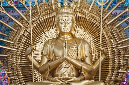 taoisme: Golden Wood Standbeeld van Guan Yin met 1000 handen Stockfoto