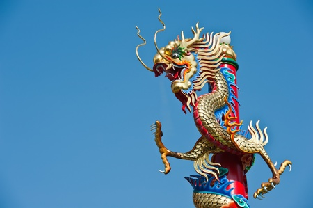 Golden dragon statue on red pillar in Chinese temple  photo