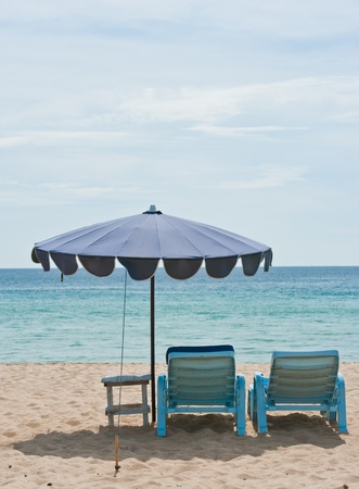 view of two chairs and umbrella on the beach  photo
