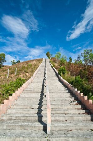 Stairs to top of mountain with white fluffy clouds and blue sky