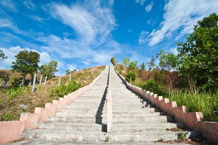 Stairs to top of mountain with white fluffy clouds and blue sky  photo