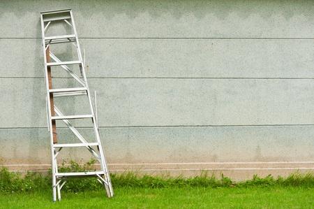 spiraglio: Scala contro muro con l'erba Archivio Fotografico