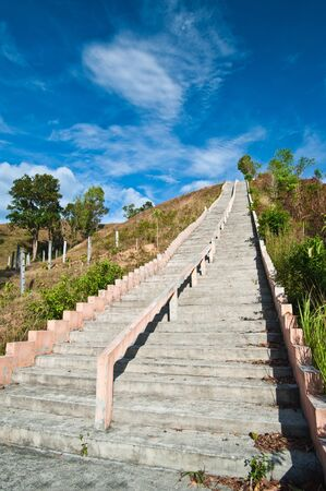 analogy: Stairs to top of mountain with white fluffy clouds and blue sky