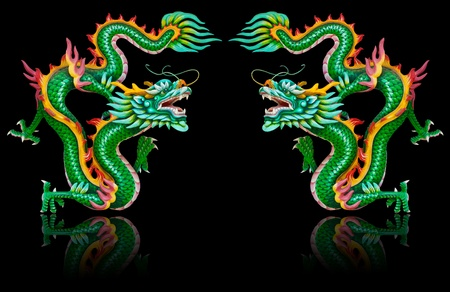 Twin green dragon statues on black background with reflection
