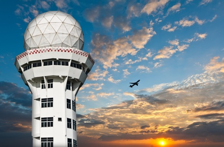 Air traffic control tower with airplane silhouette over sunset Stock Photo