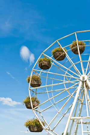 Ferris wheel with basket of flowers on the blue sky background photo