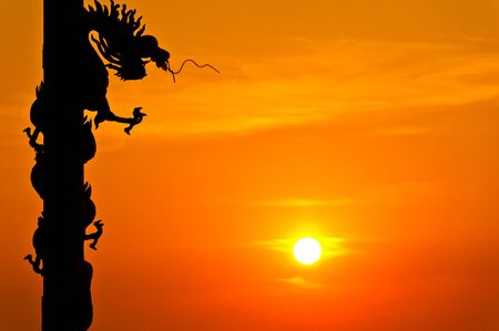 Silhouette of dragon statue with sunset photo