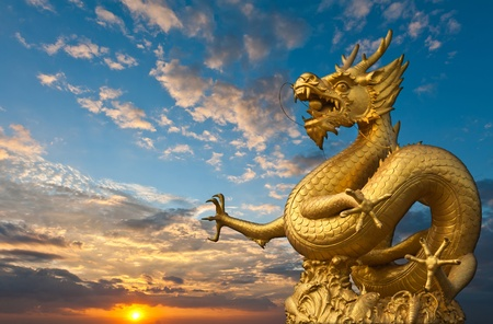 china art: Chinese Golden Dragon Statue with sunset
